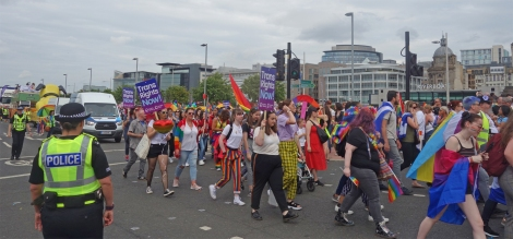 """Picture of attendees at the Pride Glasgow march, some holding """"Trans Rights Now"""" placards"""
